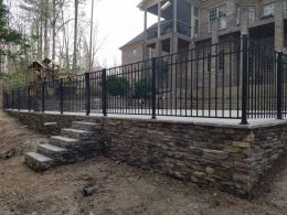 Retaining wall with fence on top of caps
