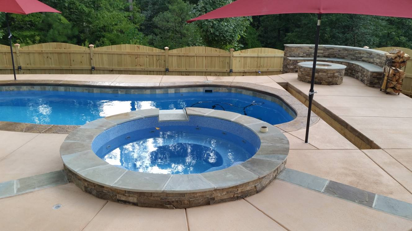hot tub surround with seat wall and firepit and colored concrete