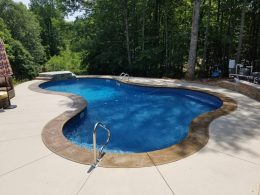 pool patio with stamped coping and stain behind
