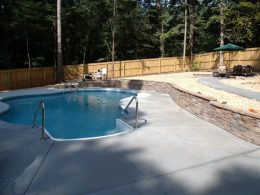 tan wall with uncolored broomed and metal coping